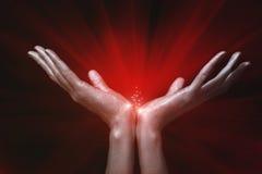 Hände der silbernen Männer, die rotes magisches Glühen anhalten Lizenzfreie Stockfotografie