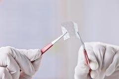 Hände der wissenschaftlichen Vertretung ein Stück Graphen mit sechseckigem Molekül. Lizenzfreie Stockbilder