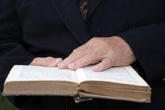 Hände des Älteren auf altem Buch Stockbild