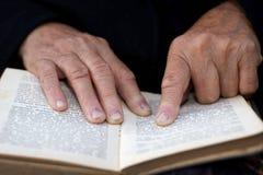 Hände des Älteren auf altem Buch Lizenzfreie Stockfotos