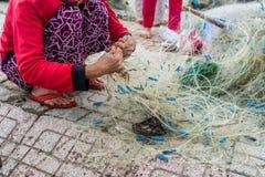 Hände des alten Fischers entwirrt Fischernetze, Nha Trang stockbilder