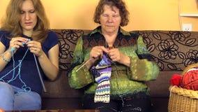 Hände des alten Großmutterknit und -junge pflegen Enkelin auf Sofa stock video footage