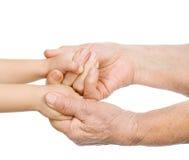 Hände des alten Mannes halten eine Hand des Babys. Lizenzfreie Stockfotografie