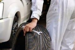 Hände des Automobilmechanikers in der Uniform mit Reifen und Schlüssel für Reparierenauto am Reparaturgaragenhintergrund Lizenzfreies Stockfoto