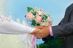 Hände des Bräutigams und der Braut mit einem Hochzeitsblumenstrauß Stockfoto