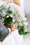 Hände des Bräutigams und der Braut mit Hochzeitsblumenstrauß Stockbilder