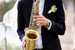 Hände des Bräutigamspiels auf Saxophon Lizenzfreies Stockfoto