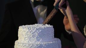 Hände des Braut- und Bräutigamschnittes einer Scheibe von einem Hochzeitskuchen Braut und Bräutigam am Hochzeitsempfang, der die  Lizenzfreie Stockfotos