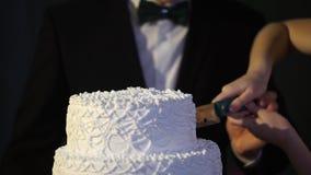 Hände des Braut- und Bräutigamschnittes einer Scheibe von einem Hochzeitskuchen Braut und Bräutigam am Hochzeitsempfang, der die  Stockfoto