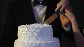 Hände des Braut- und Bräutigamschnittes einer Scheibe von einem Hochzeitskuchen Braut und Bräutigam am Hochzeitsempfang, der die  Stockfotos