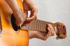 Hände des erwachsenen helfenden Kindes, zum der Akustikgitarre zu spielen Lizenzfreie Stockfotos