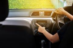 Hände des Fahrers Autoradiosystem, Knopf einschaltend auf Armaturenbrett in der Autoplatte stockfotografie