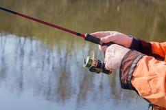 Hände des Fischers mit dem Spinnen lizenzfreie stockfotografie