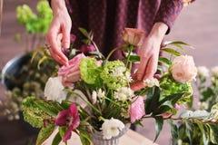 Hände des Floristen sammeln Hochzeitsblumenstrauß bei der Arbeit lizenzfreies stockfoto