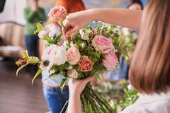 Hände des Floristen sammeln Hochzeitsblumenstrauß bei der Arbeit lizenzfreie stockfotos