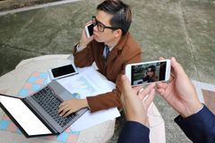 Hände des Fotografen ein Foto des hübschen jungen Geschäftsmannes bei der Unterhaltung machend am Telefon mit seinem Smartphone Stockbild