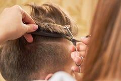 Hände des Friseurs, der Scheren und des Kammes Lizenzfreies Stockbild