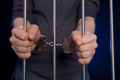 Hände des Gefangenen auf einem Stahlgitter Stockbild