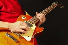Hände des Gitarristen die Gitarre auf dunklem Hintergrund spielend Stockfotografie