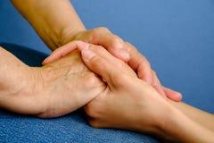 Hände des Händchenhaltens der jungen Frau einer älteren Frau Stockfotografie
