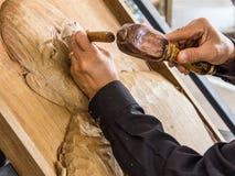Hände des Handwerkers schnitzen ein Flachrelief Stockfotografie