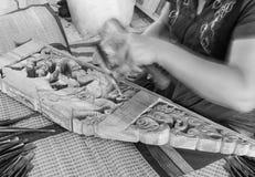 Hände des Handwerkers schnitzen handgemacht ein Flachrelief mit einem Hohlmeißel Stockfotos