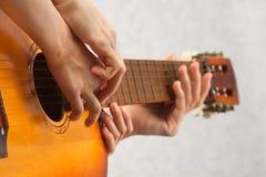 Hände des helfenden Kindes des Lehrers, zum der Akustikgitarre zu spielen Lizenzfreie Stockfotos