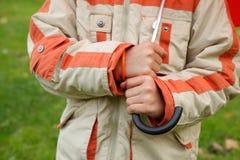 Hände des Jungen im Jackeneinfluß-Regenschirmgriff Stockfoto