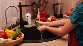 Hände des jungen Mädchens, die eine Gurke waschen stock footage