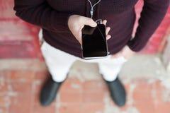 Hände des jungen Mannes einen Smartphone mit Drähten halten Stockbild