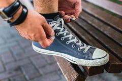 Hände des jungen Mannes seine Spitzee, Nahaufnahme binden Lebensstil-Tätigkeits-Schuhe-Konzept lizenzfreies stockfoto