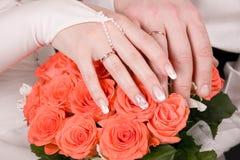 Hände des Jungvermähltens mit Ringen auf dem Blumenstrauß O Lizenzfreies Stockbild