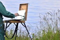 Hände des Künstlers mit einer Bürste, malen ein Bild auf einem Gestell im Freien Lizenzfreies Stockbild