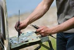 Hände des Künstlers mit Pinseln Stockfotos