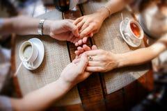Hände des Kerls und der Hand des Mädchens an einem Tisch mit einer Tasse Tee und einen Tasse Kaffee Stockbild