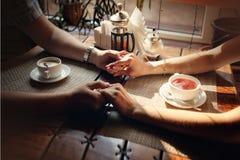 Hände des Kerls und der Hand des Mädchens an einem Tisch mit einer Tasse Tee und einen Tasse Kaffee Lizenzfreie Stockfotografie