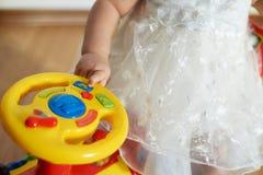 Hände des kleinen Mädchens auf Helm des gelben Babyautos Stockfoto