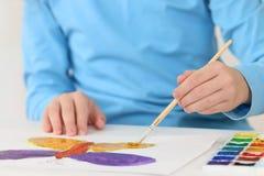 Hände des Mädchenaquarell-Malereischmetterlinges auf Tabelle Stockfotos