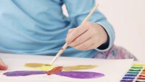 Hände des Mädchenaquarell-Malereischmetterlinges auf Tabelle im Raum, Abschluss oben stock footage