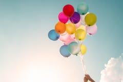 Hände des Mädchens mehrfarbige Ballone halten Lizenzfreie Stockfotos