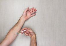 Hände des Mannes eine Einspritzung von der medizinischen Wegwerfspritze auf grauem Hintergrund machend Stockfotografie