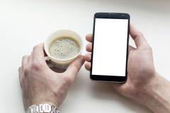 Hände des Mannes mit Kaffee auf dem Tisch mit einem weißen Schirmtelefon Stockbild
