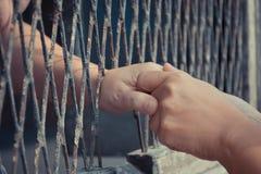 Hände des Mannes und der Frau auf einem Stahlgitter Stockbilder
