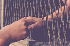 Hände des Mannes und der Frau auf einem Stahlgitter Stockfoto