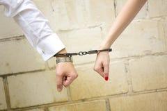 Hände des Mannes und der Frau mit den Handschellen Stockfoto