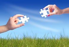 Hände des Mannes und der Frau mit Puzzlespielen Stockfoto