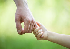 Hände des Mannes und des Kindes, die auf hellgrünem backgro zusammenhalten Lizenzfreie Stockfotografie