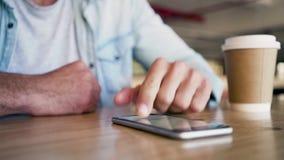 Hände des Mannes unter Verwendung des Handys auf Tabelle stock footage