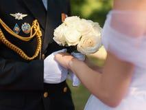 Hände des Offiziers in den Handschuhen und der Braut mit Hochzeitsblumenstrauß Stockfotos