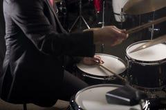 Hände des Schlagzeugers in der dunklen Beleuchtung Stockfoto